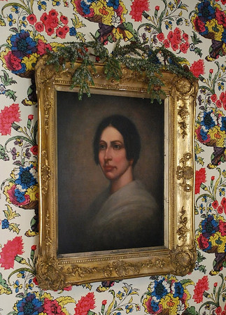 """Vivid, spectacular hand-blocked wallpaper in the Main Hall, with portrait of Hawthorne's cousin Susanna Ingersoll--who he called """"The Duchess."""" At the time of her death, Susanna was the second most wealthy woman in Salem. Hawthorne particularly loved her gossip; many of the tales she told about the misdeeds of departed Salem-ites were woven into his fiction."""