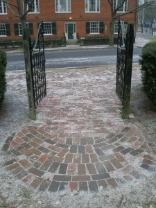 Snow is just beginning to settle upon the bricks, across from Hamilton Hall