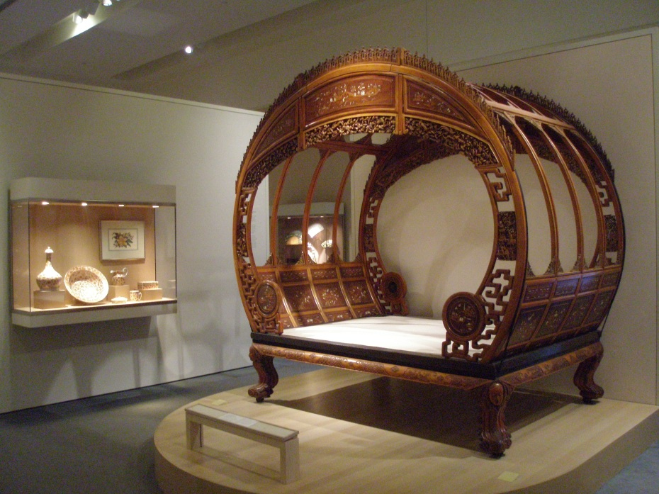 Chinese Moon Bed. 1876. Satinwood, other woods & ivory. Held together with wooden pegs & 4 butterfly-shaped wedges. There are no screws or nails, and Bed breaks down into 53 major parts.