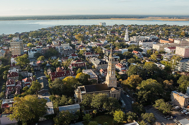 Aerial View of Historic Charleston, with the brown steeple of St. Philip's Church fore-and-center. This steeple was once used as a harbor channel light. The Mills House Hotel is the square pink building, half way up at the farthest edge of this photo. Directly adjacent to the Mills House Hotel is the white, columned portico of Hibernian Hall.