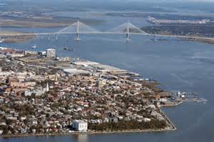 A seagull's view of the Arthur Ravenel Jr. Bridge and the Cooper River, with Historic Charleston in the foreground.