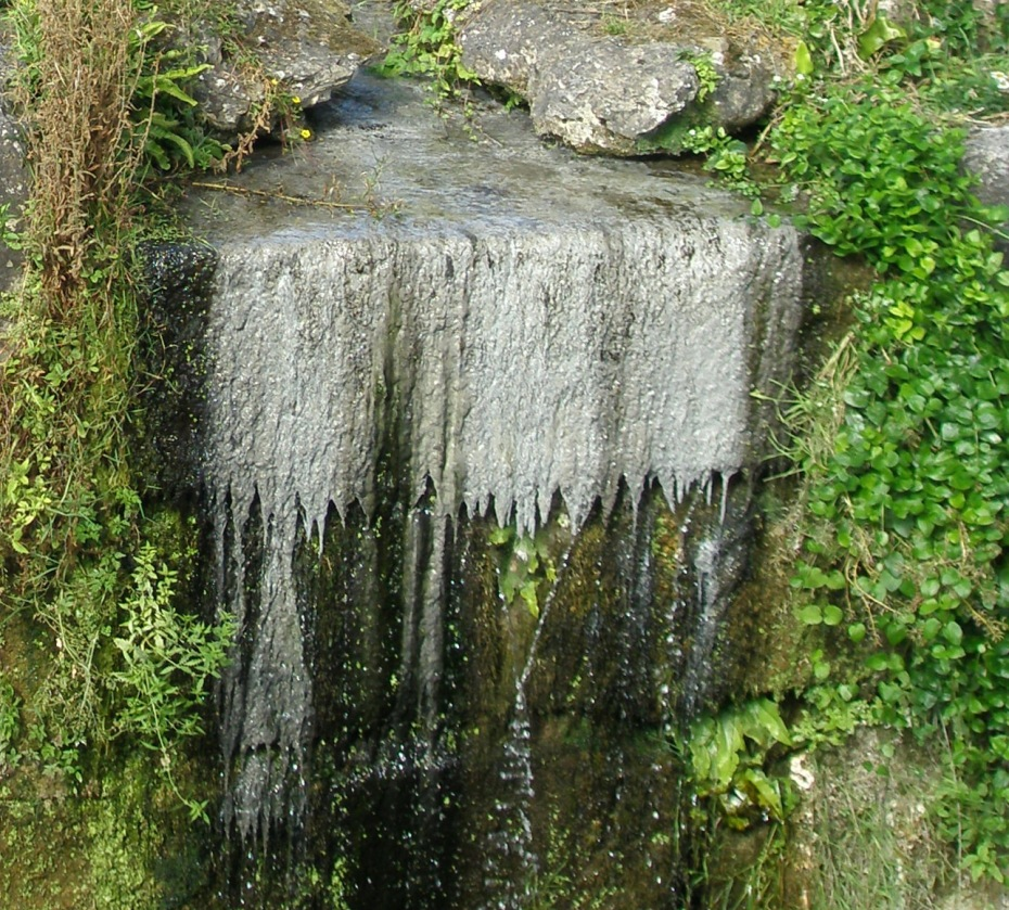 Naturally-formed limestone deposits form a lacy curtain at the High Cascade
