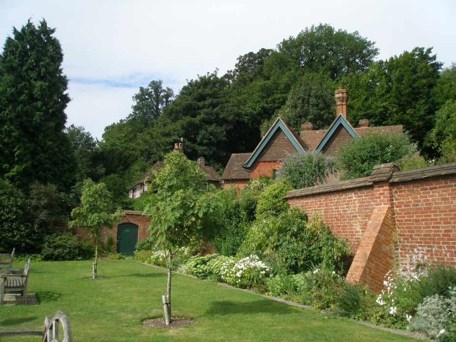 """Buttressed brick walls enclose the Orchard. A row of Kentish-tile-hung cottages is behind the wall. Clementine referred to these as """"her village."""""""