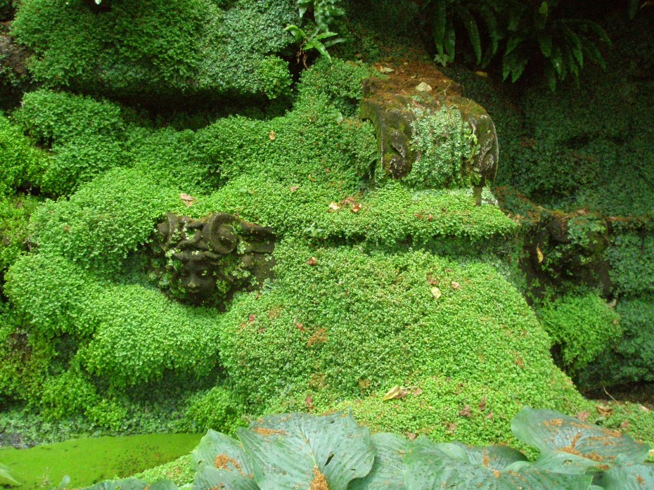 Statues in the Grottoes are nearly swallowed up by greenery.