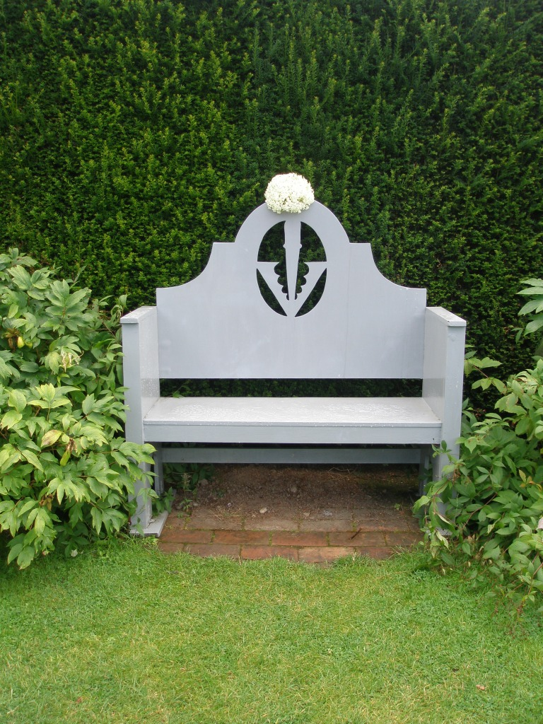 A bench in the Grey & White Garden, crowned with the Sidney Coat of Arms...and a hydrangea corsage.
