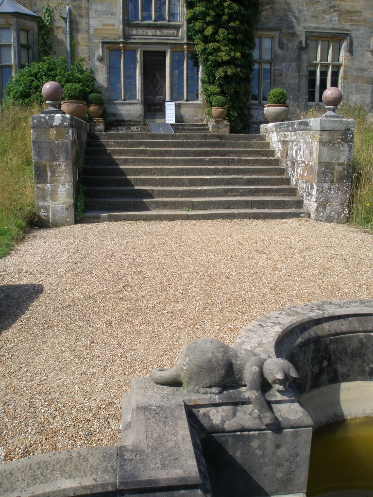 A Stone Kitten, on the Garden Front Terrace, with a view back toward the door to the Garden Lobby of the New House.