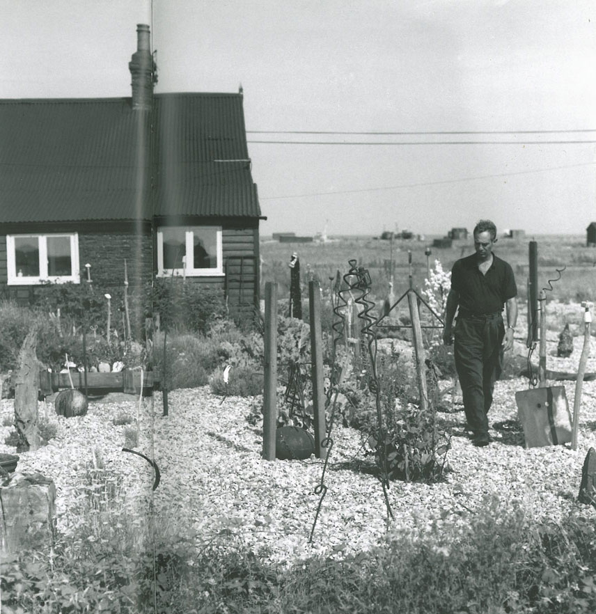 "Derek in his back garden. When he arrived at Prospect Cottage he observed ""it looked impossible: shingle with no soil supported a sparse vegetation."" Image courtesy of Estate of Derek Jarman."