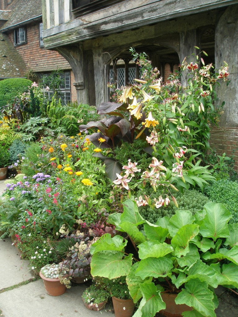 A jungle of potted flowers and plants flanks the front entry.