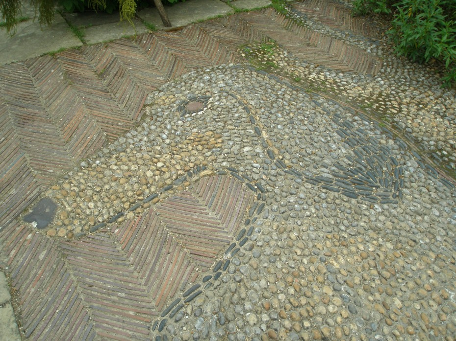 Within the Wall Garden is a terrace, with a pebble mosaic of Christopher Lloyd's two beloved dachshunds, Dahlia and Canna. The stones for Canna's eye and nose were acquired from Derek Jarman's rock-garden, at Prospect Cottage, in Dungeness.