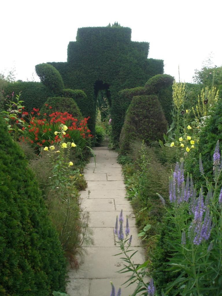 A central path through the Peacock Topiary Garden leads toward an arch, which serves as entry to the High Garden.