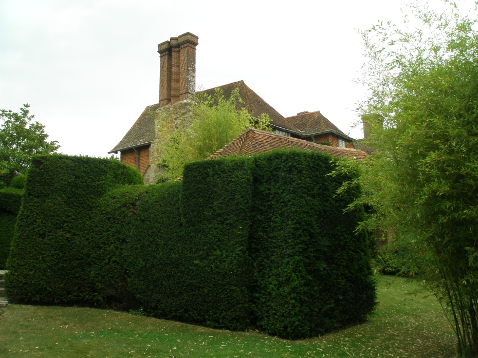 The abstract forms of hedges, and house.