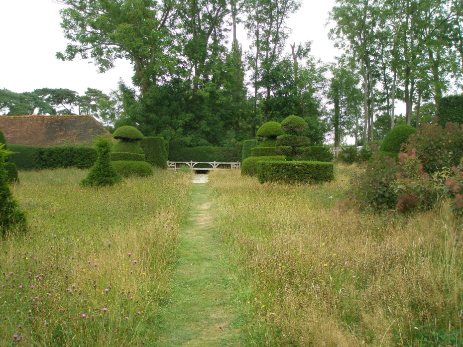 A path mown through the Topiary Lawn, toward a large bench. The roof of the Nursery Sales Shed is visible, to the left.