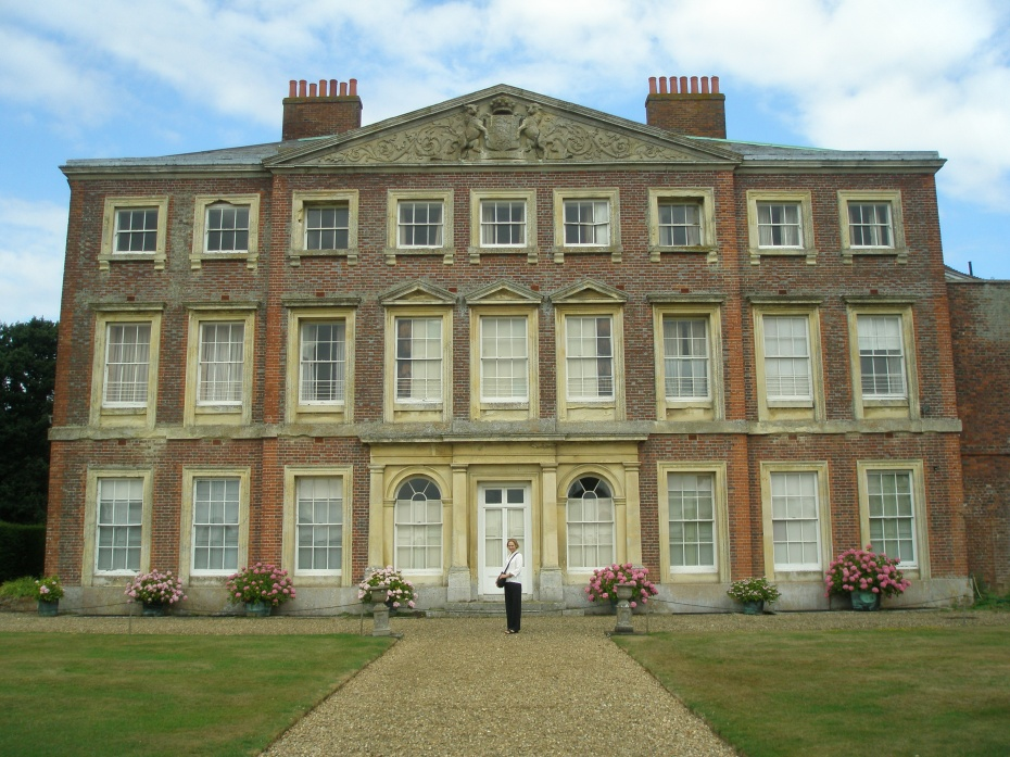 The House at Goodnestone Park, near Canterbury. Nan provides human scale here, in front of the manor, which was built for Mister Brook Bridges, in 1700. Goodnestone (pronounced GUN-Stone) Park is famous because of its link to Jane Austen. In 1791, Elizabeth (daughter of Sir Brook Bridges, 3rd Baronet) married Edward Austen, a brother of Jane Austen. During the early years of their marriage, Elizabeth and Edward Austen lived at Rowling, a manor house close to Goodnestone Park, where Elizabeth's parents resided. Jane Austen was a frequent visitor, and made many references to Goodnestone Park in her letters. This photo was taken on August 8, 2013.