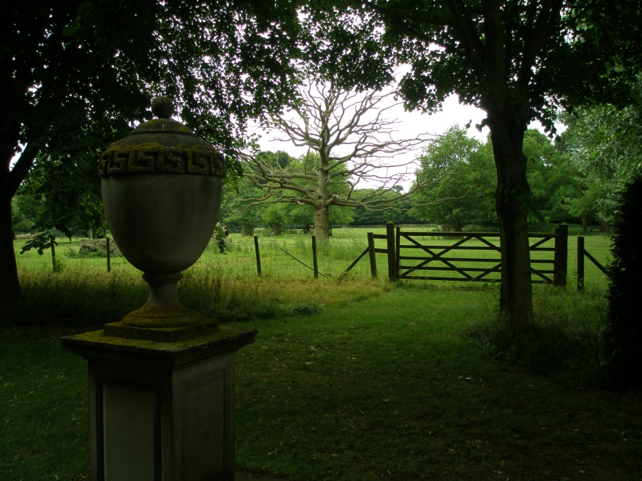 The Urn, at the far end of the Avenue of Lime Trees, with pastureland beyond the fence.