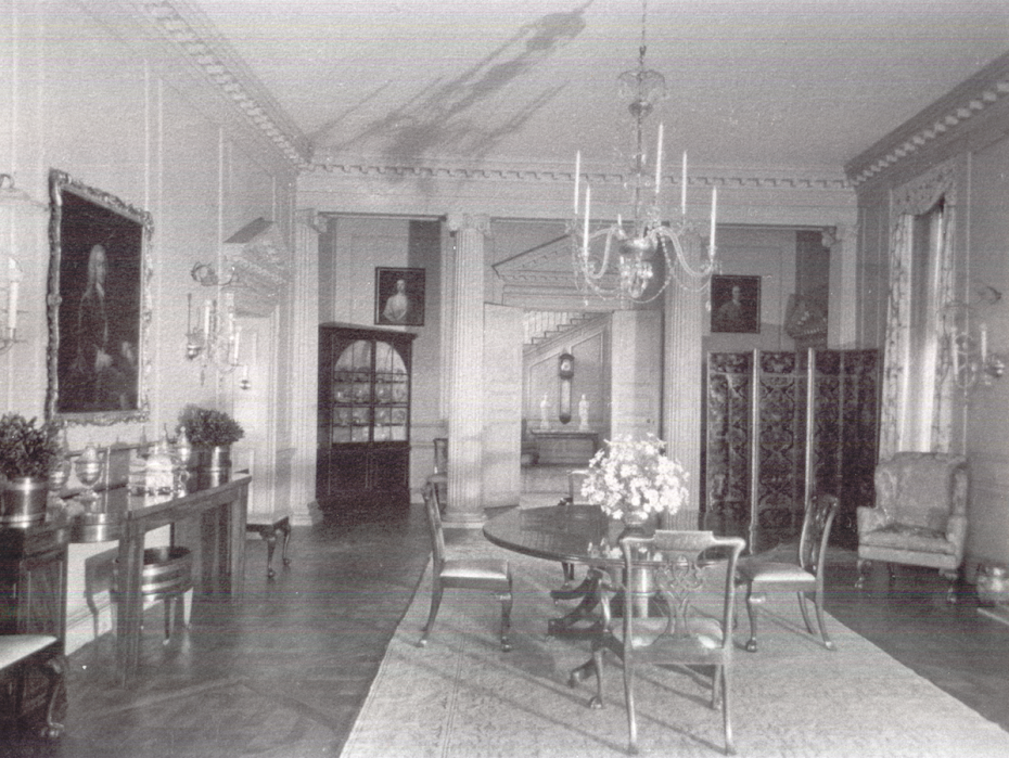 Vintage photo of the Dining Room, with a glimpse of the Stair Hall. Behind the folding screen to the right is the entrance to the Butler's Pantry. Image courtesy of the Massachusetts Historical Society.