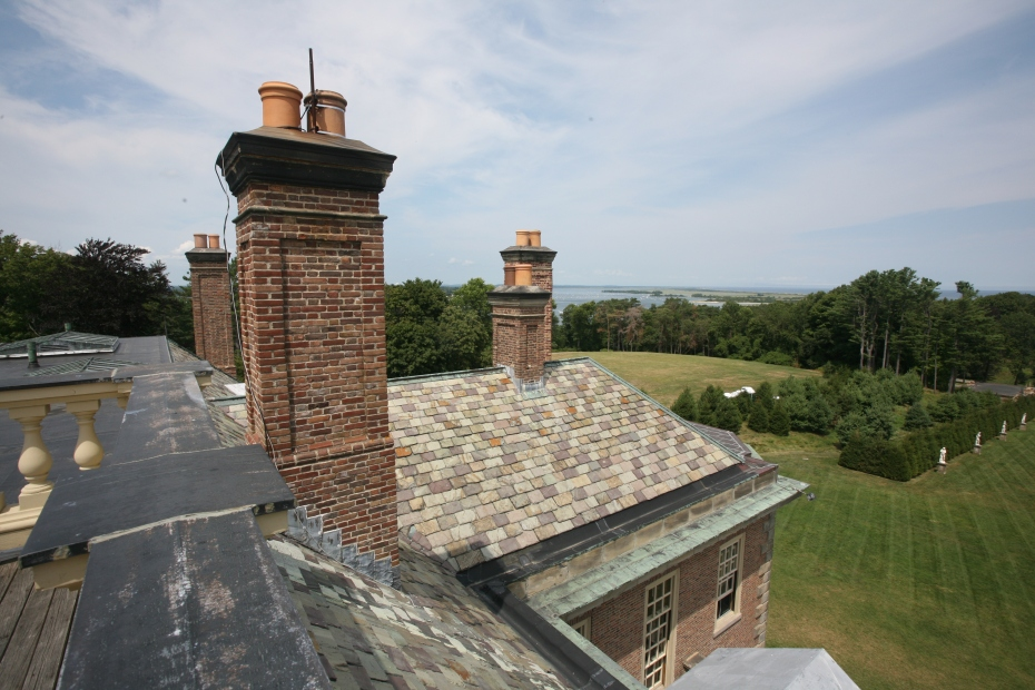 Detail of slate roof and chimneys, with Ipswich Harbor in the distance.