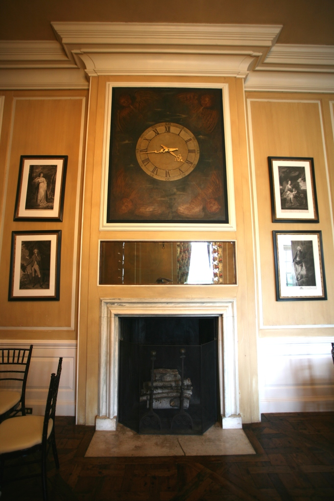 Two imposing fireplaces are centered on interior walls of The Gallery. One fireplace is crowed by a large clock.
