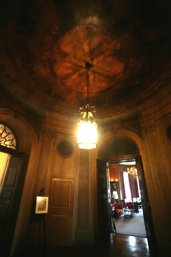 The dimly-illuminated Rotunda: which is entered from the east end of The Gallery. The Rotunda is a circular hallway which leads to the Library, former Guest quarters (not open to the Public), and also to the Living Room (a space that's now used as a Ballroom).