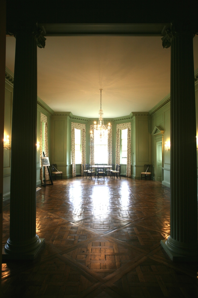 "My first glimpse of the Dining Room, as seen from the Great House Stair Hall. David Adler divided this long, slender space ""with a pair of free-standing fluted columns, which were flanked by a pair of engaged columns, all with Ionic capitals."""