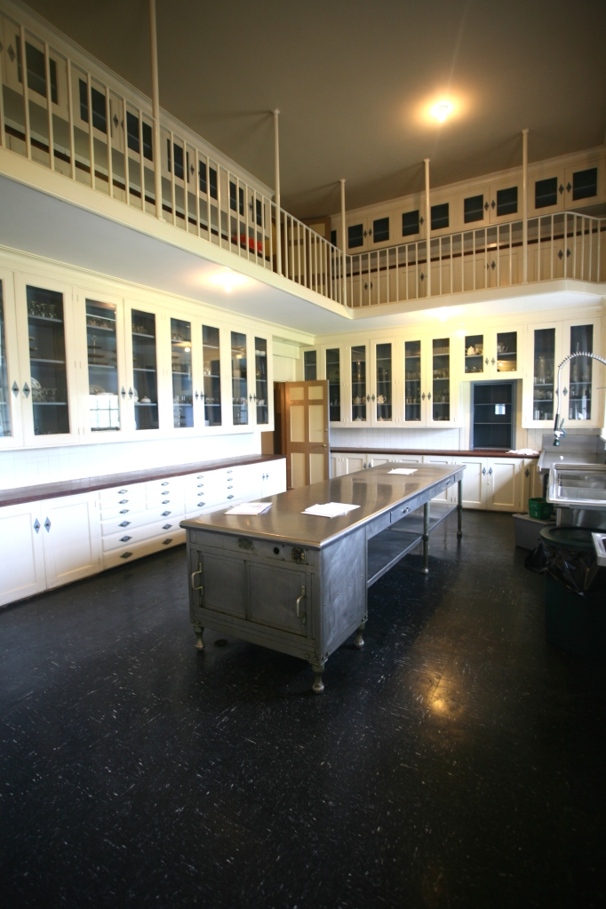 """Per the Trustees, the Butler's Pantry was """"an interim serving station for the dining room, complete with a warming cupboard within the central stainless steel table. Serving staff could receive plates from the revolving cupboard connected to the kitchen. A tier of cabinets surrounds the room, while another tier, for storage of fine china, is located on the mezzanine above."""""""