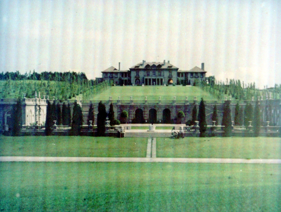 Hand-colored photo of the oceanside elevation of the Original Italian Villa, as of 1915. The Grand Allee, designed by Arthur Shurcliff, has been installed. And the Casino Complex, designed by Shepley, Rutan & Coolidge, is in the foreground (tucked into a hillside slope. Image courtesy of the Trustees of Reservations, Archives & Research Center.