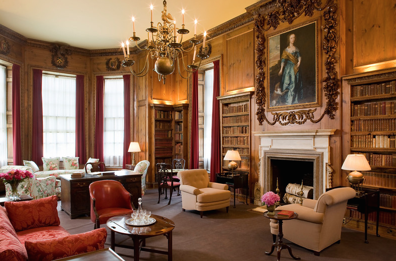 The Library, as we see it today. The elaborate carvings over the fireplace are by Grinling Gibbons, and were obtained from the English country house called Cassiobury Park, when Cassiobury was demolished in 1922. All furnishings and books have been chosen by the Trustees to resemble the furnishings used by the Crane family. Image courtesy of the Trustees of Reservations.