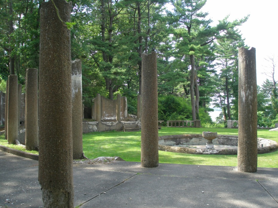 A forest of columns, on a raised terrace which girdles the Rose Garden on three sides. In the distance you can see a glimmer of water, which is Ipswich Harbor.