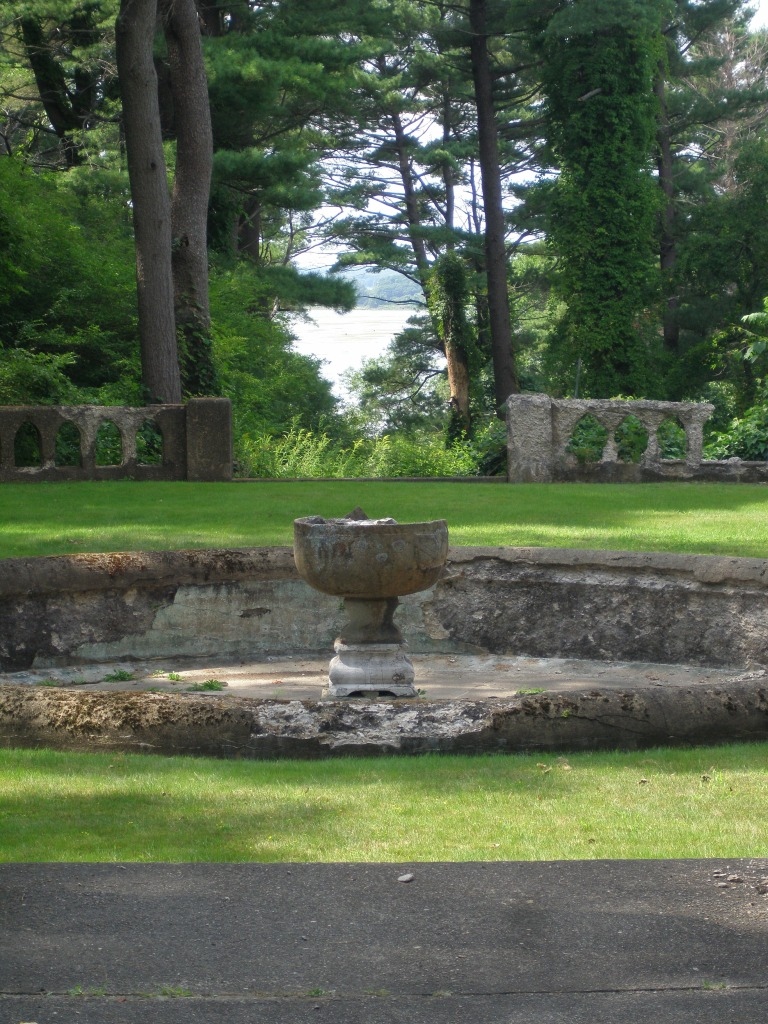 The now-dry fountain and pool at the center of the Rose Garden, with a better view of Ipswich Harbor