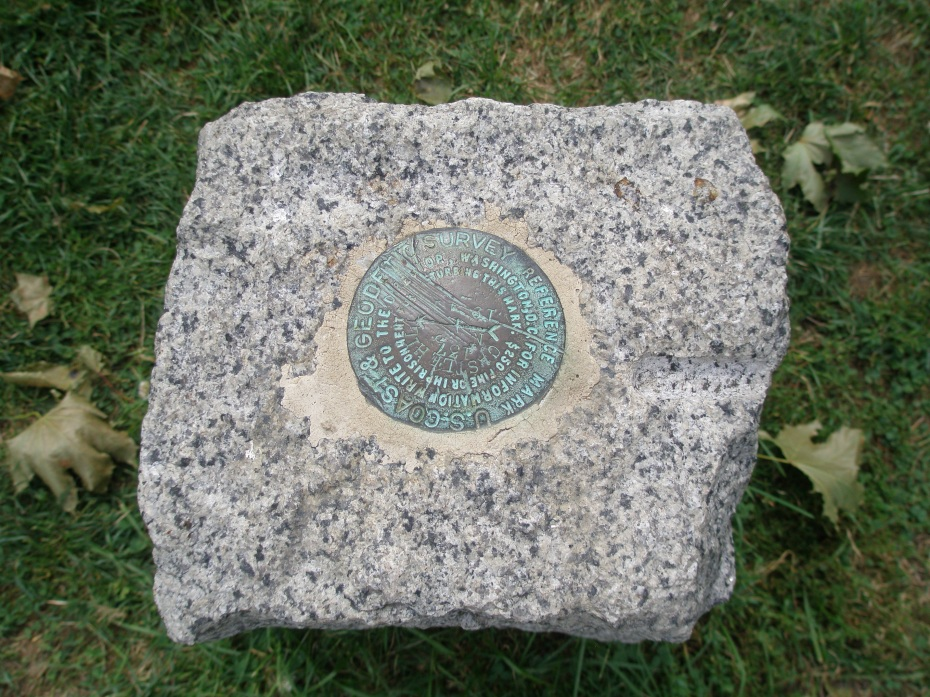 "This is the only ""garden ornament"" at the Ocean End of the Allee: a tiny Geodetic Survey Marker...which is rather an anti-climax after Arthur Shurcliff's masterfully-orchestrated, half-mile-long swath of green. A series of low stone benches placed here on the promontory would quietly punctuate the Allee's termination, and would also provide a welcome resting spot."