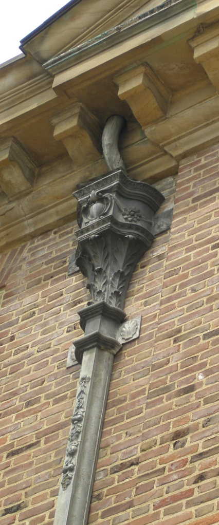 "Every inch of the Great House was carefully designed by architect David Adler. Per the Trustees: ""Mr.Adler, a perfectionist for details, designed the ornamental cast-lead downspouts to echo the fruit and floral motifs"" seen in the wood carvings done by Grinling Gibbons, which decorate the House's Library."