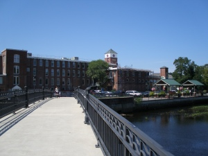 Pedestrian bridge across the Ipswich River, leading to the new River Walk, and the old mill buildings.
