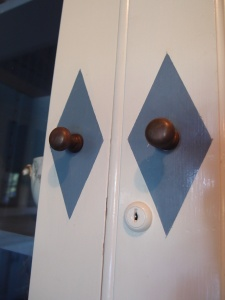 Detail of cupboard doors in Butler's Pantry. The room has been restored to its original color scheme of off-white and deep blue. Ever clever and practical, Adler had these blue diamonds painted around each cupboard knob to hide the smudges left by the food-stained hands of kitchen workers.