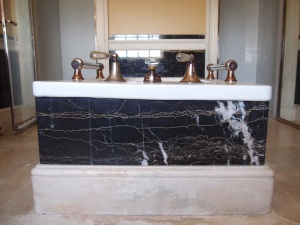 The business end of Mr. Crane's bathtub, with silver fixtures and handrails.