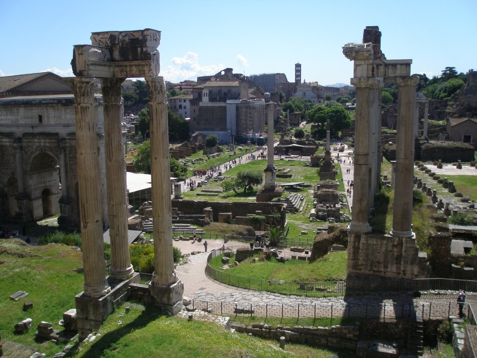 Another view from the Tabularium. Set back, in the center of the grassy rectangle are the Colonna di Foca (added in 609AD), & the Rostrum, which was a Speaker's Platform. The large green expanse marks the Square of the Roman Forum. To the left of the Forum, the long walkway is the Via Sacra. In the left foreground: 3 columns mark the corner of the Temple of Concord. In the right foreground, the tall columns and pediment are the front of the Temple of Saturn.