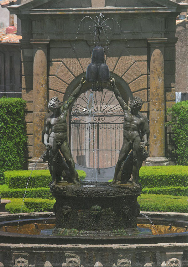 In better weather: the figures on the Island in the Fountain of the Moors garden. In the background is a gate, beyond which is the Village. Image courtesy of Il Pegaso Bookshop, in Bagnaia.
