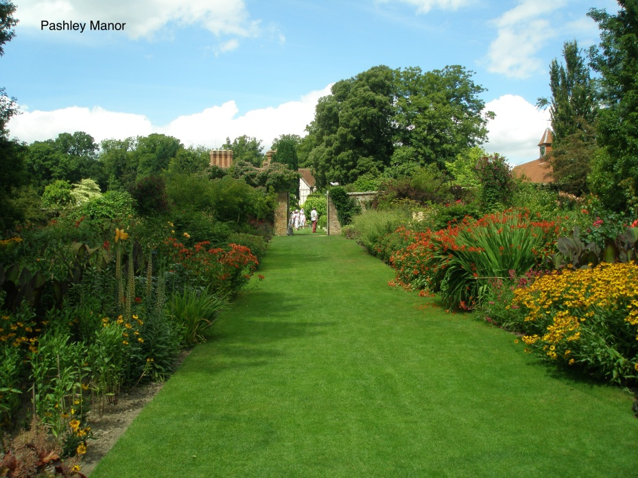 A double border of hot-colored perennials leads us toward the Walled Garden