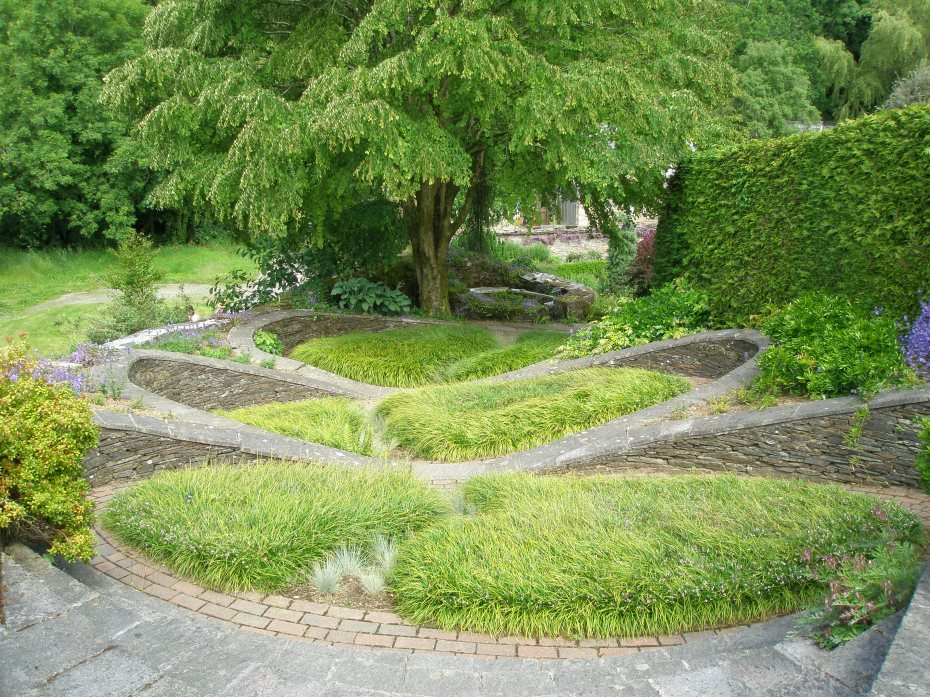 From the western end of the Bowling Green Terrace one first passes through a rustic summerhouse, which opens onto this extraordinary cascade of steps, ramps and raised beds: called THE OVAL GARDEN.