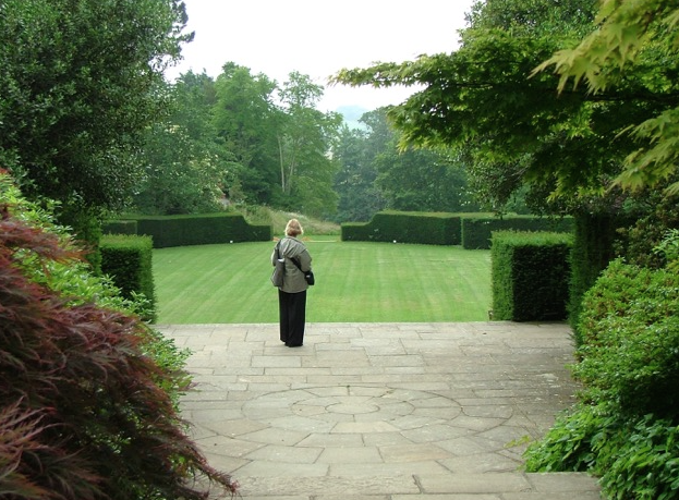 Nan, on the Terrace by the Swan Fountain, overlooks the Green of the Tiltyard. Part of the charm of the Tiltyard are the ways in which views of its precipitous slopes are often hidden, from other areas in Dartington's Gardens. Photo by Anne Guy.