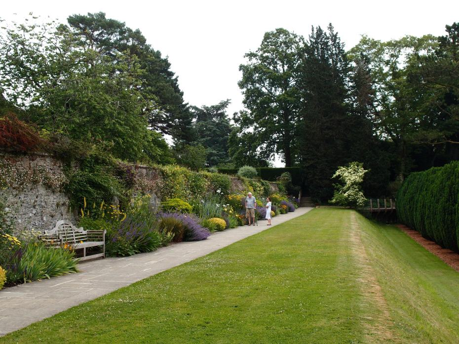 On the left: the Sunny Border. To the rear, right: the line of highly-sculptural Irish Yews, which are called the Twelve Apostles.