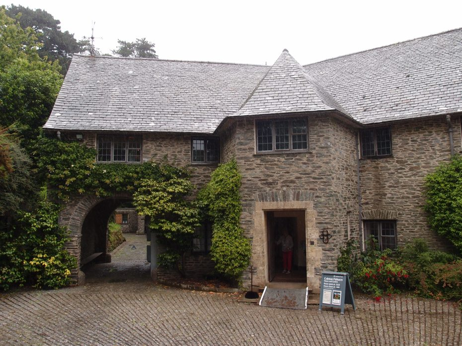 Front of House, with archway to Service Court. The Service Court is tucked into the hillside, to the north of the House. The exterior of the House is constructed from Dartmouth shale stone, which was blasted from rock in the lower part of the D'Oyly Cartes' valley. That same shale was also used to build the garden's terraces and walls. The roof is shingled with Delabole slate. [Note: The Delabole slate quarry is in nearby Cornwall. The quarry has been in continuous operation since the 15th century, and is the oldest working slate quarry in England.]