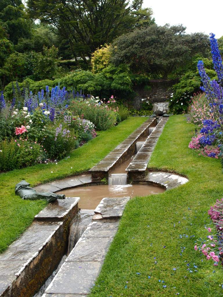 The Rill Garden was designed by Oswald Milne. This hillside garden is bisected by a narrow, canalized stream and a small, central pool. Lady Dorothy originally planted many pastel-colored rose bushes here, but those shrubs failed, in the seaside air. Semi-tender perennials now fill the Rill Garden.