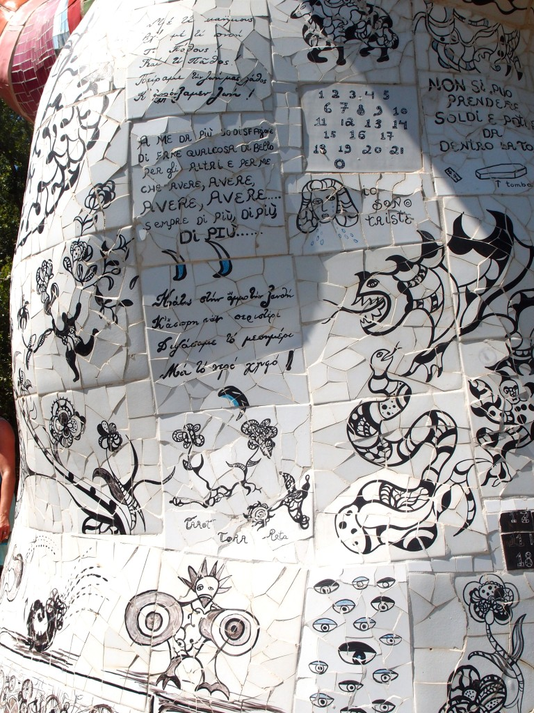 "Detail of exterior of the Tree of Life. The tiles on the outside of this structure are densely covered with Niki's scrawls. Translated, they're a timeline of a love affair, which ends in heartbreak. With drawings and these words, Niki begins: ""I would like to give you everything, my mouth, my money, my imagination, my breast, my time, my terrific cooking, my everything."" Many tiles later, she writes ""What shall I do now that you've left me? Will I cry a million tears? Will I die? Will I take to drink? Take a trip? Will I consult the stars and a crystal ball on how to win you back? Will we stay friends?"""