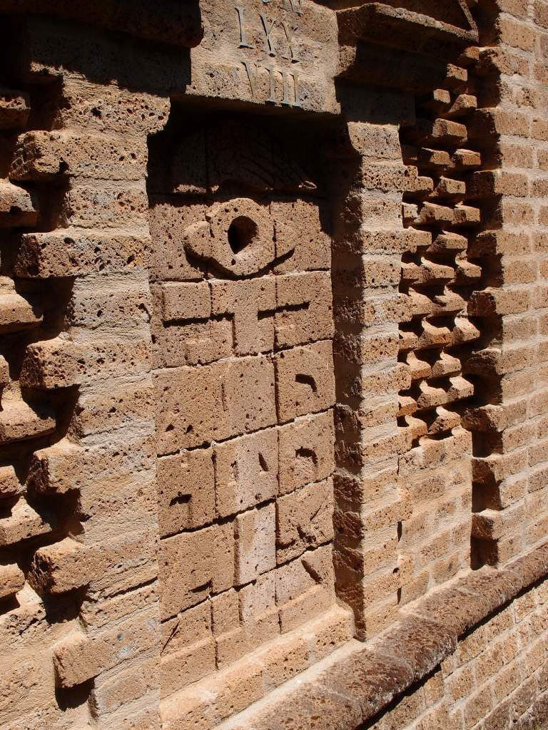 Walls usually have Ears. Buzzi's walls have EYES. This City Wall detail shows how humble building materials—roughly-fashioned blocks and bricks---have been ingeniously assembled to form intricate, shadow-casting patterns.